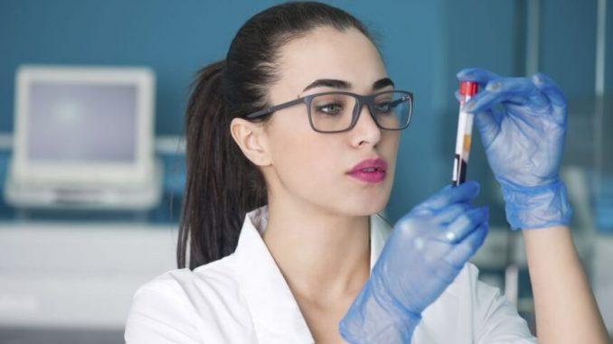 врач держит колбу с кровью