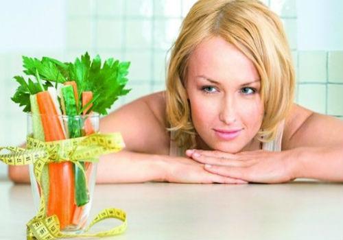 Женщина смотрит на стакан с зеленью