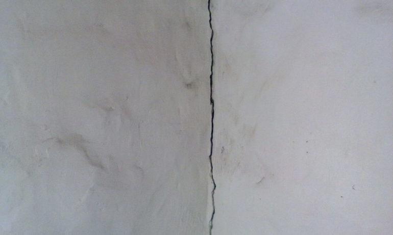 Трещины в углах и стенах.