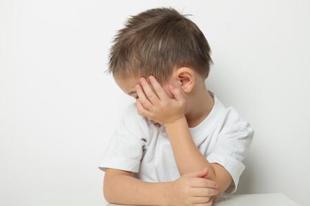 Мальчик закрыл лицо руками