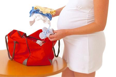 Беременная женщина собирает сумку в роддом